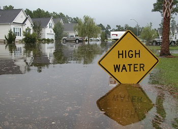 Flooded neighborhood with a sign that reads high water